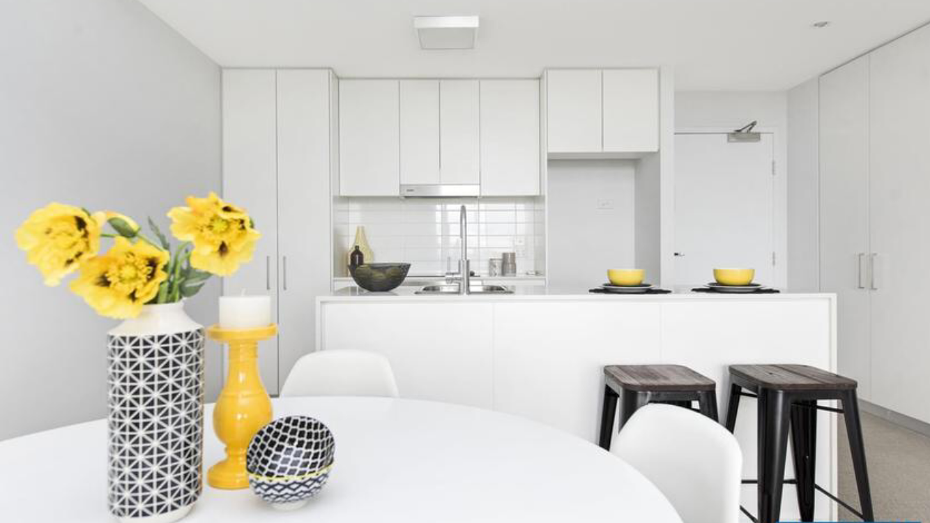 Modular kitchen designed with white theme, yellow flowers and breakfast counter with brown chairs